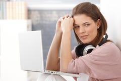 Ung kvinna som tänker och att ha bärbar dator Royaltyfri Bild