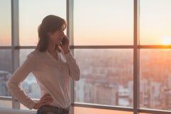 Ung kvinna som talar genom att använda mobiltelefonen på kontoret i aftonen Koncentrerad kvinnlig affärskvinna och att se framåtr fotografering för bildbyråer