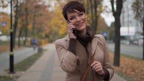 Ung kvinna som talar lyckligt på telefonen på gatan arkivfilmer