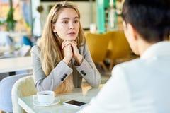 Ung kvinna som talar med personen på kafétabellen fotografering för bildbyråer