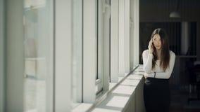 Ung kvinna som talar på cellen, stående near fönster inom kontor arkivfilmer