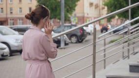 Ung kvinna som talar på hennes mobiltelefon på gatan stock video