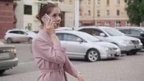 Ung kvinna som talar på hennes mobiltelefon på gatan lager videofilmer