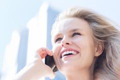 Ung kvinna som talar på mobiltelefonen över stadsbakgrund Affär arkivbild