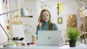 Ung kvinna som talar på mobiltelefonen, medan surfa internet på bärbara datorn stock video