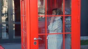 Ung kvinna som talar på telefonen i telefonbåset arkivfilmer