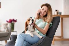 Ung kvinna som talar på telefonen, medan slå hennes hund royaltyfria bilder