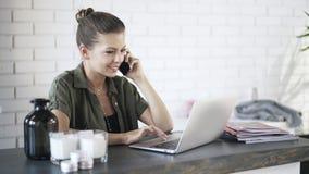 Ung kvinna som talar på telefonen och använder bärbara datorn lager videofilmer