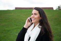 Ung kvinna som talar utomhus på mobiltelefonen Arkivbilder