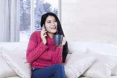 Ung kvinna som talar vid telefonen på soffan Royaltyfri Fotografi