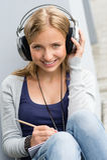 Ung kvinna som tar anmärkningar som lyssnar till musik Royaltyfri Bild