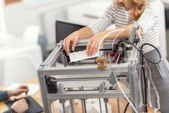 Ung kvinna som tar bort modellen från skrivaren 3D Arkivbilder
