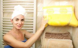 Ung kvinna som tar en handduk från handdukhållaren Fotografering för Bildbyråer