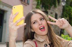 Ung kvinna som tar en selfie Arkivbild