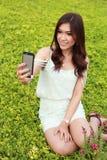 Ung kvinna som tar en självstående, genom att använda mobiltelefonen Royaltyfri Fotografi
