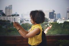 Ung kvinna som tar ett foto i cityscapen royaltyfria bilder
