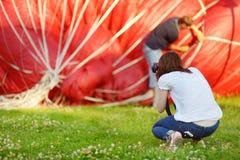 Ung kvinna som tar foto av ballonger Arkivbild