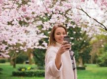 Ung kvinna som tar fotografier av vårblomningträdgården Arkivbild