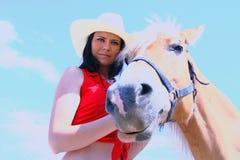 Ung kvinna som tar omsorg av henne hästen Fotografering för Bildbyråer