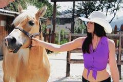 Ung kvinna som tar omsorg av henne hästen Arkivfoton