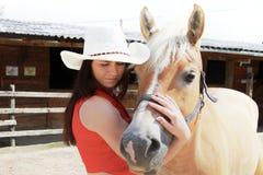 Ung kvinna som tar omsorg av henne hästen Royaltyfri Fotografi