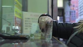 Ung kvinna som tar pengarkassa från fönster för valutautbyte medan lopp i den Hong Kong staden, Kina turist- kvinna arkivfilmer