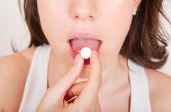 Ung kvinna som tar pills Arkivbild