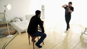 Ung kvinna som tar professionellt bilder av mannen på stol medel Kvinnafotografen tar bilden av modellen av mannen arkivfilmer