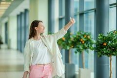 Ung kvinna som tar seldie vid smartphonen i väntande på flyg för internationell flygplats arkivbilder