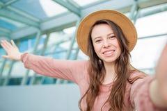 Ung kvinna som tar selfie ett väntande på logi för flygplatsvardagsrum i internationell flygplats royaltyfria foton