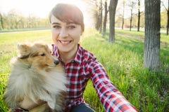 Ung kvinna som tar selfie med hennes hund royaltyfri fotografi