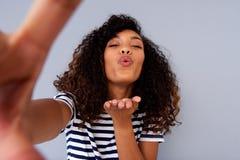 Ung kvinna som tar selfie och blåser en kyss Royaltyfri Bild