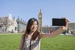 Ung kvinna som tar självståenden till och med den smarta telefonen mot Big Ben på London, England, UK Arkivbilder