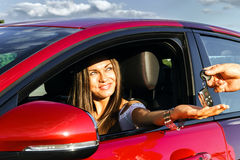 Ung kvinna som tar tangenter av den nya bilen Royaltyfri Bild
