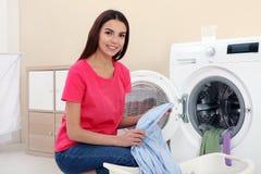Ung kvinna som tar tvätterit ut ur tvagningmaskinen arkivfoton