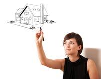 Ung kvinna som tecknar ett hus på whiteboard royaltyfria bilder