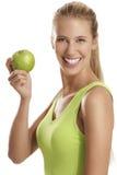 Ung kvinna som äter ett äpple Arkivfoto