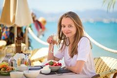 Ung kvinna som äter frukter i en strandrestaurang Arkivbild