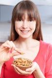 Ung kvinna som äter mandlar från bunken Royaltyfria Bilder