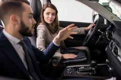 Ung kvinna som testar den nya bilen i visningslokal fotografering för bildbyråer