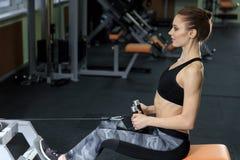 Ung kvinna som tillbaka övar på maskinen i idrottshallen och böjer muskler - muskulös idrotts- kroppsbyggarekonditionmodell arkivfoton