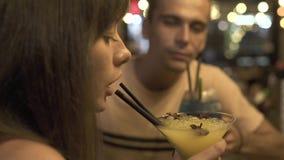 Ung kvinna som tillsammans dricker från man för coctail för sugrör alkoholiserad i nattklubb Koppla ihop mannen och kvinnan som i lager videofilmer