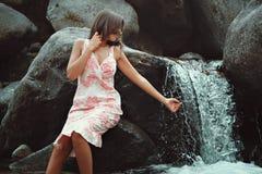 Ung kvinna som trycker på en vattenfall fotografering för bildbyråer