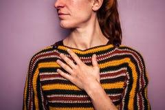 Ung kvinna som trycker på hennes bröstkorg royaltyfri bild