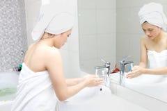 Ung kvinna som tvättar hennes händer, når att ha badat Royaltyfri Bild