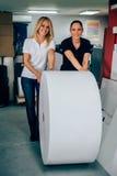 Ung kvinna som två arbetar i printingfabrik arkivfoton