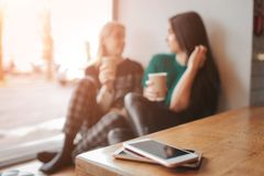 Ung kvinna som två pratar i en coffee shop Två vänner som tillsammans tycker om kaffe Deras smartphones som ligger i hög på Fotografering för Bildbyråer
