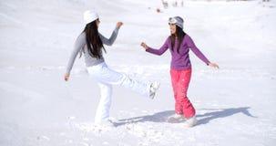 Ung kvinna som två stojar i vintersnö arkivfoto