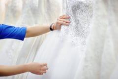 Ung kvinna som två väljer den perfekta bröllopsklänningen under brud- shopping Arkivbilder