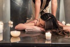 Ung kvinna som tycker om acupressureteknikerna av den thailändska massagen Arkivfoton